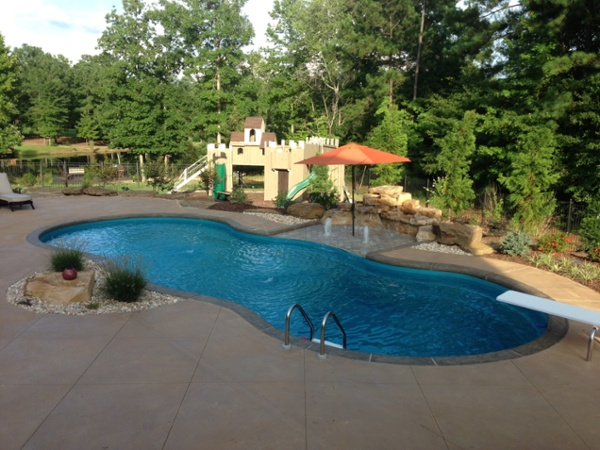 Leisure fiberglass pool with scored / stained deck,slate look coping tanning ledge and rico rock 4' double waterfall